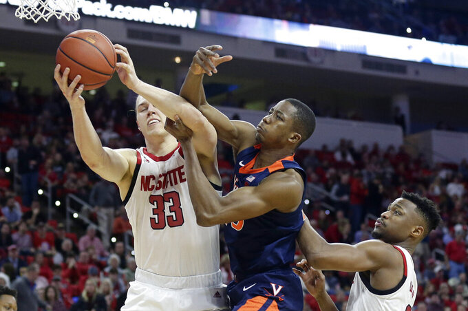 Virginia's Mamadi Diakite, center, reaches for the ball with North Carolina State's Wyatt Walker (33) and Torin Dorn during the second half of an NCAA college basketball game in Raleigh, N.C., Tuesday, Jan. 29, 2019. Virginia won 66-65 in overtime. (AP Photo/Gerry Broome)