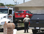 A vehicle is towed as Denton County Sheriff's officers investigate a crime scene at a home where multiple people were killed and one was hospitalized after a shooting at a home in the Remington Park neighborhood of Ponder, Texas, on Wednesday, May 16, 2018. (Rose Baca/The Dallas Morning News via AP)