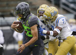 Oregon's Travis Dye, left, scores a touchdown ahead of UCLA's Jay Shaw, center, and Mo Osling III during the first quarter of an NCAA college football game Saturday, Nov. 21, 2020, in Eugene, Ore. (AP Photo/Chris Pietsch)