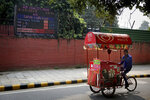 An ice-cream vendor rides past an air quality level board outside India Meteorological Department which shows condition of air as poor in New Delhi, India, Wednesday, Oct. 16, 2019. The Indian capital's air quality levels have plunged to