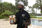 Former NFL football player Charles Woodson shows bottles of his own bourbon and wine while reflecting on his life and career as he prepares for induction into the NFL Hall of Fame, during an interview at his home Tuesday, June 15, 2021, in Orlando, Fla. (AP Photo/Phelan M. Ebenhack)