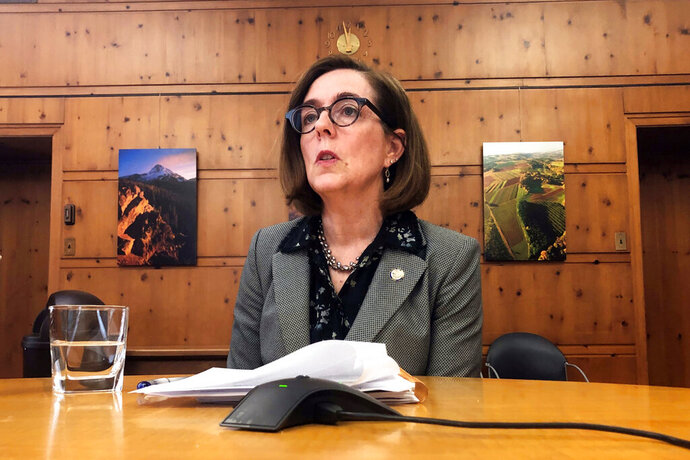 FILE - In this Monday, July 1, 2019, file photo, Oregon Gov. Kate Brown speaks with the media at the Capitol in Salem, Ore. Republican lawmakers were left fuming and justice reform advocates elated after Oregon's governor decided against calling a special session of the Legislature to have lawmakers review a new law narrowing death penalty cases. Gov. Kate Brown said late Wednesday, Sept. 18, 2019, that as much as she wanted a special session there would be none because stakeholders and legislators had failed to craft language to fix bill and line up enough votes to pass the redo. (AP Photo/Sarah Zimmerman, File)