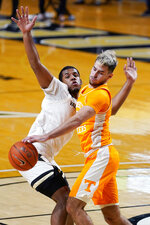 Vanderbilt's Jordan Wright, left, and Tennessee's Santiago Vescovi, right, battle for the ball in the first half of an NCAA college basketball game Wednesday, Feb. 24, 2021, in Nashville, Tenn. (AP Photo/Mark Humphrey)