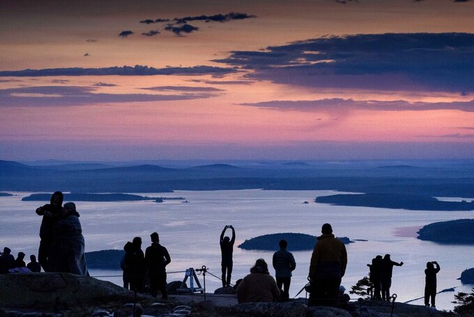 Early-rising visitors to Acadia National Park await the sunrise on the summit of Cadillac Mountain, Sunday, May 16, 2021, near Bar Harbor, Maine. Gov. Janet Mills is is eliminating most outdoor distancing requirements imposed during the COVID-19 pandemic as the tourism season begins to kick into gear. (AP Photo/Robert F. Bukaty)