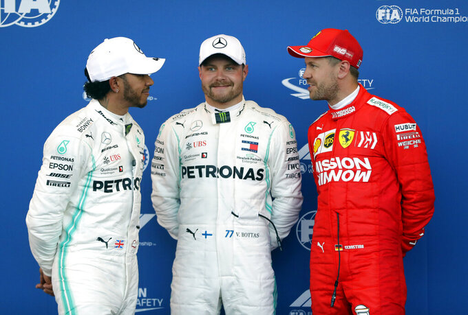 Mercedes driver Valtteri Bottas of Finland, center, celebrates his first place in the qualifying session, with second placed Mercedes driver Lewis Hamilton of Britain, left and third Ferrari driver Sebastian Vettel of Germany, at the Baku Formula One city circuit in Baku, Azerbaijan, Saturday, April 27, 2019. The Azerbaijan F1 Grand Prix race will be held on Sunday. (AP Photo/Sergei Grits)