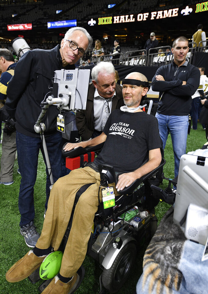 Former New Orleans Saints player Steve Gleason, who suffers from amyotrophic lateral sclerosis (ALS), looks at his screen with former Saints assistant coach Joe Vitt, center, before an NFL divisional playoff football game against the Philadelphia Eagles, in New Orleans, Sunday, Jan. 13, 2019. (AP Photo/Bill Feig)