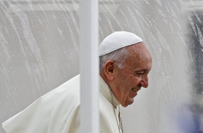 Pope Francis smiles as he arrives in his pope mobile, covered with a roof to protect him from the rain, for his weekly general audience in St. Peter's Square, at the Vatican, Wednesday, Nov. 13, 2019. (AP Photo/Gregorio Borgia)