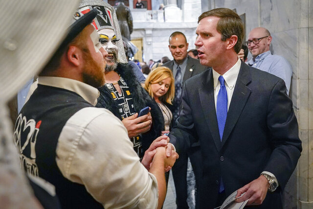 FILE - In this Wednesday, Feb. 19, 2020. file photo, Kentucky Democratic Governor Andy Beshear greets members of the Kentucky Order of the Sisters of Perpetual Indulgence, an LGBTQ charity group, following an LGBTQ rally at the Capitol building in Frankfort, Ky., Kentucky Gov. Andy Beshear defended a photograph of him posing with drag queens at a gay rights rally and accused a Republican lawmaker of using homophobic tactics by displaying the photo at a recent campaign rally while accusing Democrats of corrupting values, Thursday, Feb. 27, 2020. (AP Photo/Bryan Woolston, File)