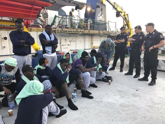 FILE -- In this file photo migrants sit on the quay after disembarking at Lampedusa harbor, Italy, on June 29, 2019. Small boats filled with more Tunisian migrants have reached a tiny Italian island, which had no room to quarantine them Saturday, Aug. 1, 2020, amid the pandemic. Sicilian daily Giornale di Sicilia quoted Lampedusa Mayor Toto' Martello as saying the island can't wait until the government sends a ferry as promised so they can be safely isolated for 14 days as part of anti-COVID-19 measures.  (AP Photo/Annalisa Camilli)