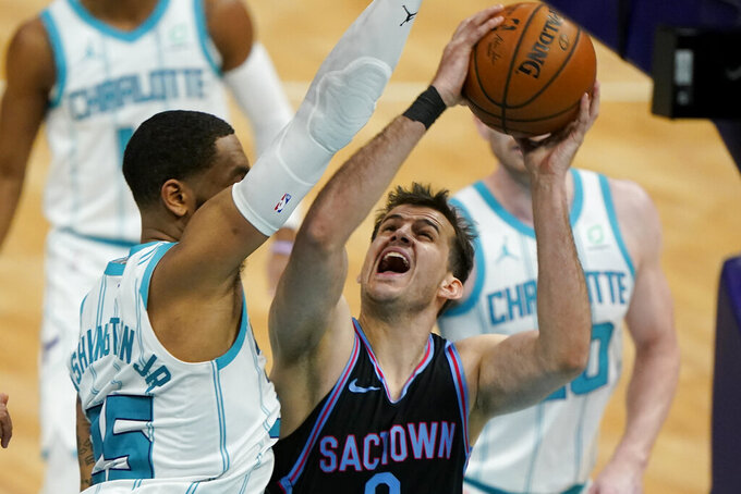 Sacramento Kings forward Nemanja Bjelica shoots over Charlotte Hornets forward P.J. Washington during the first half of an NBA basketball game on Monday, March 15, 2021, in Charlotte, N.C. (AP Photo/Chris Carlson)