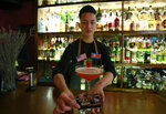 In this Feb. 22, 2019, photo, bartender Ngo Dinh Tien presents