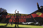 People hold a banner as thousands gather at a rally supporting the Black Lives Matter and Black Deaths in Custody movements in Sydney, Sunday, July 5, 2020. (AP Photo/Rick Rycroft)