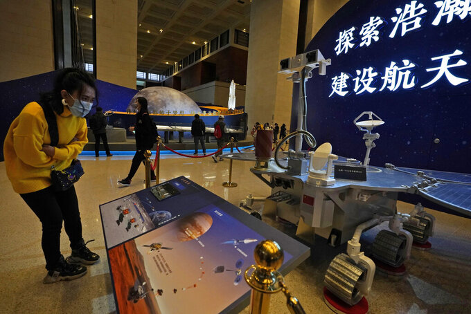 """A visitor to an exhibition looks at a display with a replica of the Chinese Mars Rover of the Tianwen-1 spacecraft in Beijing on March 12, 2021. China's National Space Agency confirmed Wednesday, March 31, 2021 that it had working-level meetings and communications with NASA from January to March """"to ensure the flight safety"""" of their crafts. (AP Photo/Ng Han Guan)"""