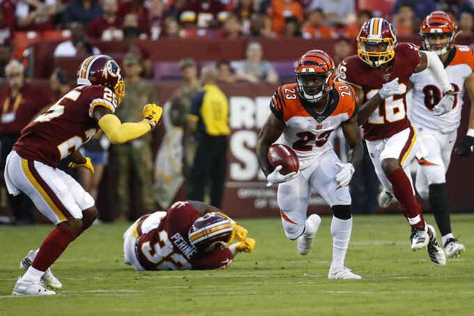 Cincinnati Bengals' Darius Phillips (23) runs with the ball with Washington Redskins' Jimmy Moreland (25) and Jehu Chesson (16) nearby on a kickoff return during the first half of an NFL preseason football game Thursday, Aug. 15, 2019, in Landover, Md. (AP Photo/Alex Brandon)