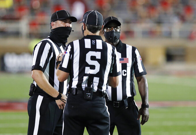 Officials wear masks during an NCAA college football game between Houston Baptist and Texas Tech on Saturday, Sept. 12, 2020, in Lubbock, Texas. (AP Photo/Mark Rogers)