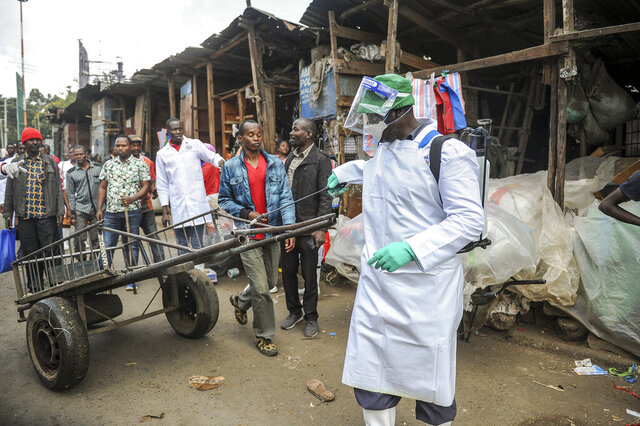 A Kenyan Health Ministry official sprays disinfectant onto a hand-cart to control the spread of the new coronavirus, in the Gikomba outdoor street market in the capital Nairobi, Kenya Saturday, March 21, 2020. For most people, the new coronavirus causes only mild or moderate symptoms such as fever and cough and the vast majority recover in 2-6 weeks but for some, especially older adults and people with existing health issues, the virus that causes COVID-19 can result in more severe illness, including pneumonia. (AP Photo/John Muchucha)