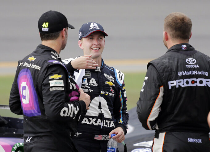 Jimmie Johnson, left, William Byron, center, and Matt DiBenedetto talk on pit road during an inclement weather delay in the NASCAR Cup Series auto race at Daytona International Speedway, Sunday, July 7, 2019, in Daytona Beach, Fla. (AP Photo/Terry Renna)