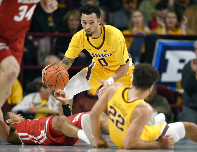 Minnesota's Payton Willis (0) gets the ball after Wisconsin's D'Mitrik Trice and Minnesota's Gabe Kalscheur (22) fell to the court during the first half of an NCAA college basketball game Wednesday, Feb. 5, 2020, in Minneapolis. (AP Photo/Hannah Foslien)