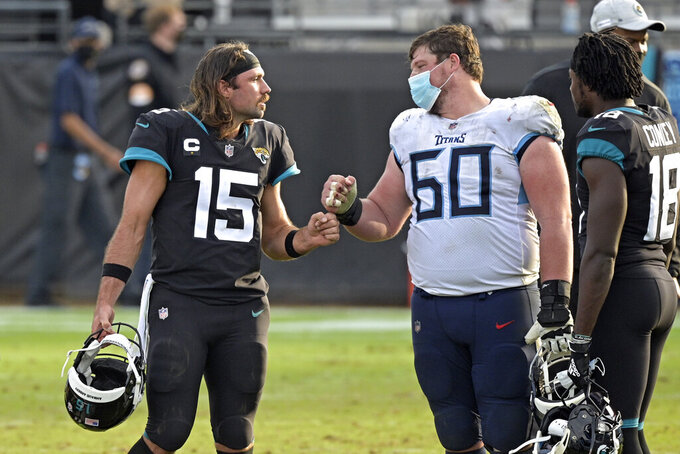 Jacksonville Jaguars quarterback Gardner Minshew II (15) and Tennessee Titans center Ben Jones (60) fist bump after an NFL football game, Sunday, Dec. 13, 2020, in Jacksonville, Fla. (AP Photo/Phelan M. Ebenhack)