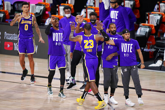 Los Angeles Lakers' LeBron James (23) celebrates with teammates during a timeout in the final moments of an NBA conference final playoff basketball game against the Denver Nuggets Saturday, Sept. 26, 2020, in Lake Buena Vista, Fla. The Lakers won 117-107 to win the series 4-1. (AP Photo/Mark J. Terrill)