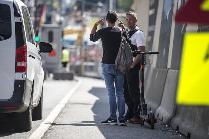 The police talks to a tourist after he drove an electric scooter in the Opera tunnel in Oslo, Friday, July 12, 2019. Police in Oslo say they have stopped a foreign tourist who was caught on surveillance cameras riding through part of a vast and busy tunnel system in the center of the Norwegian capital on an electric scooter.  Police tweeted that the male tourist, who wasn't identified, had followed a route given by Google Maps to explain why he had entered the nearly 16-kilometer (10-mile) long Opera Tunnel complex. (Trond Reidar Teigan/NTB Scanpix via AP)