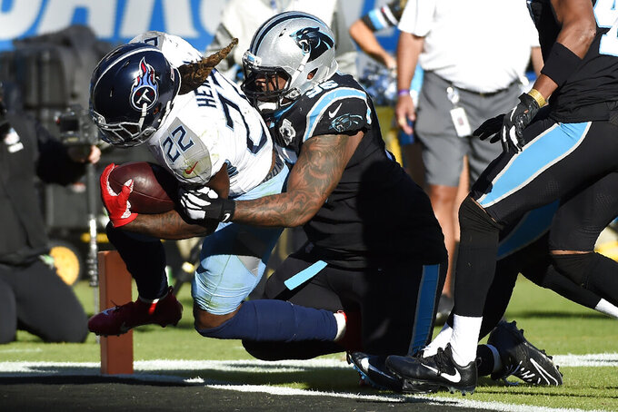 Tennessee Titans running back Derrick Henry (22) scores a touchdown while Carolina Panthers defensive tackle Dontari Poe (95) tackles during the second half of an NFL football game in Charlotte, N.C., Sunday, Nov. 3, 2019. (AP Photo/Mike McCarn)
