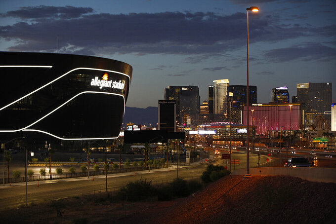 "FILE - In this July 22, 2020, file photo, the sun sets behind Allegiant Stadium, new home of the Las Vegas Raiders football team, as it nears completion in Las Vegas. Officials in Nevada have declared ""substantial completion"" after nearly 1,000 days of construction of the $2 billion Allegiant Stadium in Las Vegas designed to be the home of the NFL's relocated Raiders. (AP Photo/John Locher, File)"