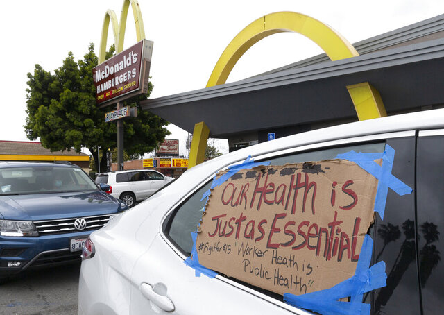 FILE - In this April 6, 2020, file photo, protesters stop momentarily at a McDonald's drive-thru, as they join fast-food workers protesting for a second day outside the restaurant in the Crenshaw district of Los Angeles. Essential workers will strike nationwide on May Day to demand safer conditions during the coronavirus outbreak, while other groups plan rallies against tight stay-at-home orders they say are crippling the U.S. economy. (AP Photo/Damian Dovarganes, File)