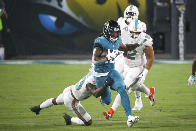 Jacksonville Jaguars wide receiver Laviska Shenault Jr., center, runs for yardage after a reception before being tackled by Miami Dolphins cornerback Noah Igbinoghene during the first half of an NFL football game, Thursday, Sept. 24, 2020, in Jacksonville, Fla. (AP Photo/Stephen B. Morton)