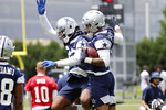 Dallas Cowboys cornerback Trevon Diggs, left, celebrates with Micah Parsons, right, after Parsons made an interception during NFL football practice in Frisco, Texas, Thursday, June 3, 2021. (AP Photo/Michael Ainsworth)