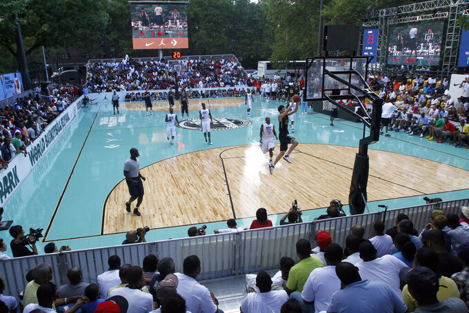 FILE - In this ç, spectators watch one of the basketball matches during the World Basketball Festival at Rucker Park in New York. The COVID-19 pandemic has left the New York street ball scene quiet since Mayor Bill de Blasio ordered the rims at 80 playground courts around the city to be removed because people weren't adhering to social distancing. While the city is set to slowly begin reopening this month, recreation activities aren't set to be addressed for several weeks. It's left open the possibility that New York's hallowed outdoor courts such as Rucker Park, all as much a part of New York's basketball culture as the Knicks and Madison Square Garden, could remain silenced into summer. (AP Photo/Mary Altaffer, FIle)