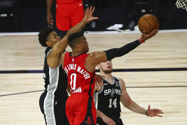 Houston Rockets guard Russell Westbrook, center, goes up for a shot while San Antonio Spurs forward Keldon Johnson, left, defends during the first half of an NBA basketball game Tuesday, Aug. 11, 2020, in Lake Buena Vista, Fla. (Kim Klement/Pool Photo via AP)