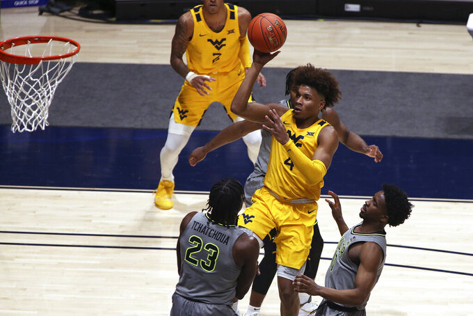 West Virginia guard Miles McBride (4) shoots while defended by Baylor forward Jonathan Tchamwa Tchatchoua (23) and guard Adam Flagler (10) during the first half of an NCAA college basketball game Tuesday, March 2, 2021, in Morgantown, W.Va. (AP Photo/Kathleen Batten)