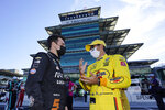 Pato O'Ward, of Mexico, left, talks with Helio Castroneves, of Brazil, before the final practice session for the Indianapolis 500 auto race at Indianapolis Motor Speedway, Friday, Aug. 21, 2020, in Indianapolis. (AP Photo/Darron Cummings)