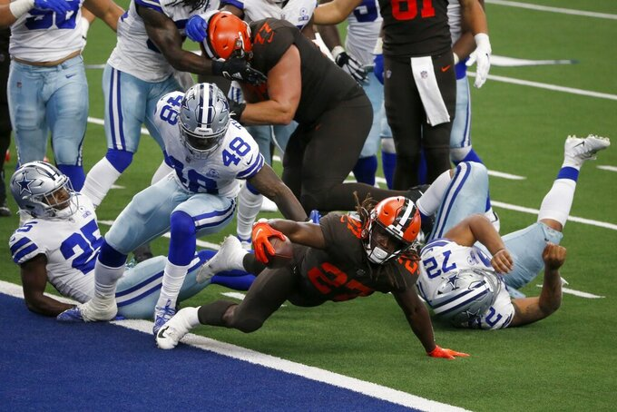 Cleveland Browns running back Kareem Hunt (27) reaches over the goal line to score a touchdown after getting through Dallas Cowboys' Xavier Woods (25), Joe Thomas (48), and Trysten Hill (72) in the first half of an NFL football game in Arlington, Texas, Sunday, Oct. 4, 2020. (AP Photo/Michael Ainsworth)
