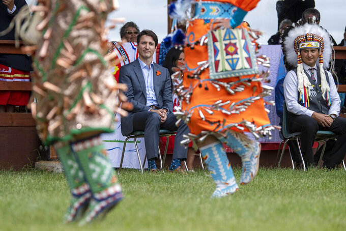 Prime Minister Justin Trudeau, left, and Chief Cadmus Delorme watch dancers during a ceremony celebrating the signing of a transfer of control over children in care to the community, in Cowessess First Nation, Saskatchewan, Tuesday, July 6, 2021. Cowessess is also the site of a former residential school where, the month before, ground-penetrating radar detected a potential 751 unmarked graves. (Liam Richards/The Canadian Press via AP)