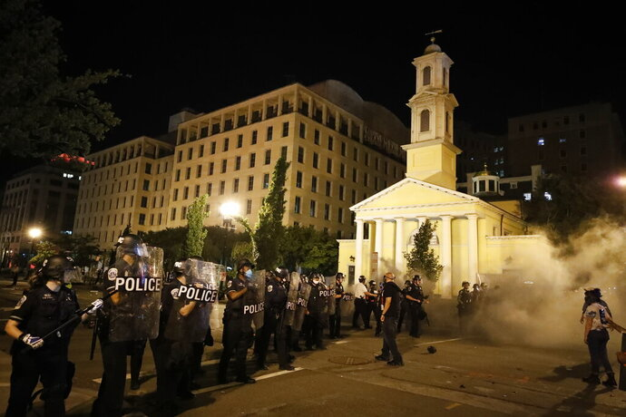 FILE - In this Saturday, May 30, 2020 file photo, police for a line near St. John's Episcopal Church as demonstrators gather to protest the death of George Floyd, near the White House in Washington. Floyd, a Black man, died after being restrained by Minneapolis police officers. St. John's, at the epicenter of protests in Washington, has a long legacy on civil rights dating to its embrace of the 1963 March on Washington. (AP Photo/Alex Brandon)