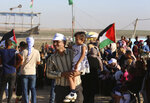 In this Sept. 25, 2019 photo, Palestinian activist Ahmed Abu Artima holds his daughter during an alternative protest he organized near the separation fence between the Gaza Strip and Israel, east of Gaza City. Gaza's Hamas rulers are facing a rare and growing chorus of criticism, with little to show after 18 months of mass protests along the Israeli border organized by the Palestinian militant group. Gazans are increasingly questioning the high number of casualties and lack of success in lifting the Israeli blockade. Against this backdrop, Artima has launched his own peaceful version of the protest. (AP Photo/Adel Hana)