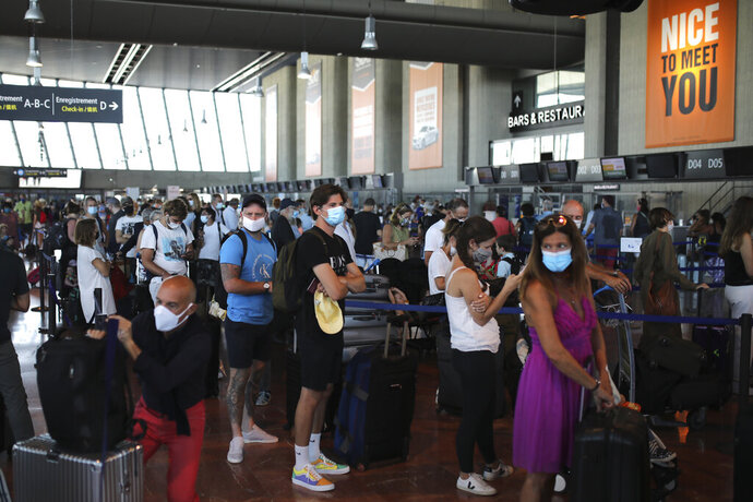 People queue in line to check-in for a British Airways flight to Heathrow airport, Friday Aug.14, 2020 at Nice airport, southern France. British holidaymakers in France were mulling whether to return home early Friday to avoid having to self-isolate for 14 days following the U.K. government's decision to reimpose quarantine restrictions on France amid a recent pick-up in coronavirus infections. (AP Photo/Daniel Cole)