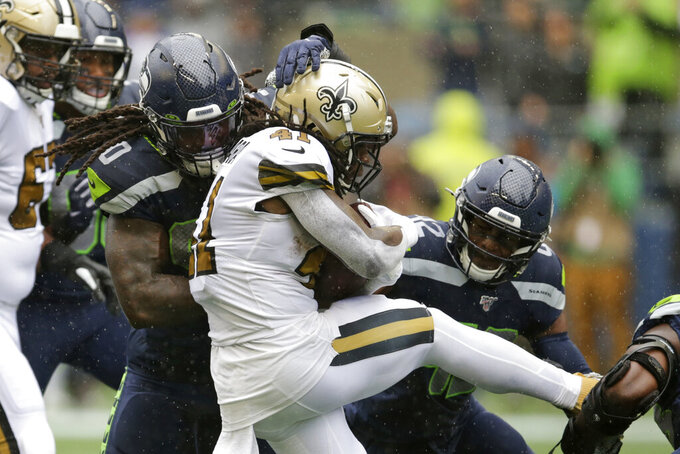Seattle Seahawks' Jadeveon Clowney, left, and Lano Hill move in on New Orleans Saints' Alvin Kamara on a carry during the first half of an NFL football game, Sunday, Sept. 22, 2019, in Seattle. (AP Photo/Scott Eklund)