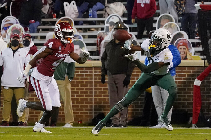 Baylor wide receiver Tyquan Thornton (9) catches a pass for a touchdown in front of Oklahoma cornerback Jaden Davis (4) during the second half of an NCAA college football game Saturday, Dec. 5, 2020, in Norman, Okla. (AP Photo/Sue Ogrocki)