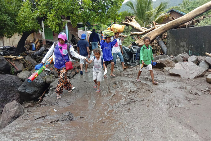 People walk amid debris at a village affected by flood in Ile Ape, on Lembata Island, East Nusa Tenggara province, Indonesia, Sunday, April 4, 2021 photo. Multiple disasters caused by torrential rains in eastern Indonesia have left dozens of people dead or missing while displacing thousands, the country's disaster relief agency said Monday. (AP Photo/Ricko Wawo)