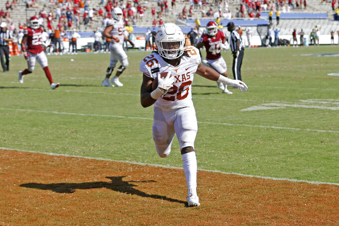 Texas running back Keaontay Ingram (26) scores a touchdown against Oklahoma during the second half of an NCAA college football game in Dallas, Saturday, Oct. 10, 2020. Oklahoma defeated Texas 53-45 in four overtimes.(AP Photo/Michael Ainsworth)