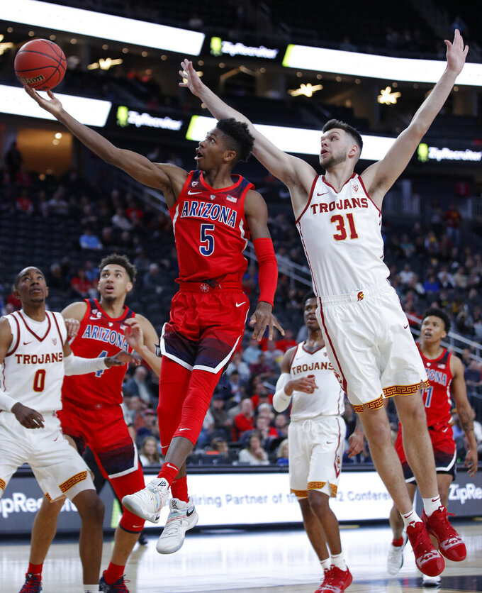 Arizona's Brandon Randolph (5) shoots around Southern California's Nick Rakocevic (31) during the second half of an NCAA college basketball game in the first round of the Pac-12 men's tournament Wednesday, March 13, 2019, in Las Vegas. (AP Photo/John Locher)