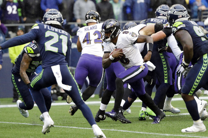 Baltimore Ravens quarterback Lamar Jackson (8) keeps the ball for a touchdown on a fourth-down play against the Seattle Seahawks during the second half of an NFL football game, Sunday, Oct. 20, 2019, in Seattle. (AP Photo/Elaine Thompson)