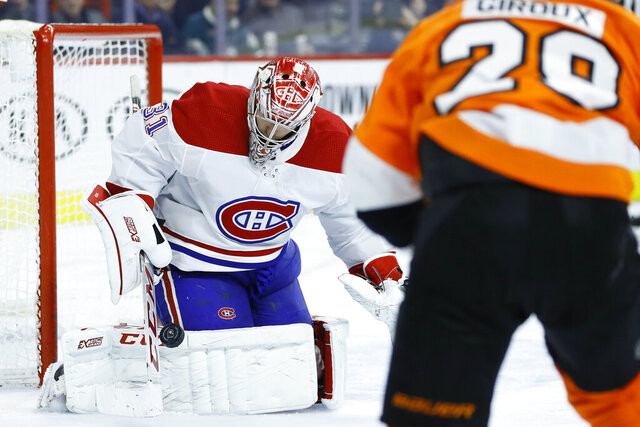 Montreal Canadiens' Carey Price, left, blocks a shot past Philadelphia Flyers' Claude Giroux during the second period of an NHL hockey game, Thursday, Jan. 16, 2020, in Philadelphia. (AP Photo/Matt Slocum)