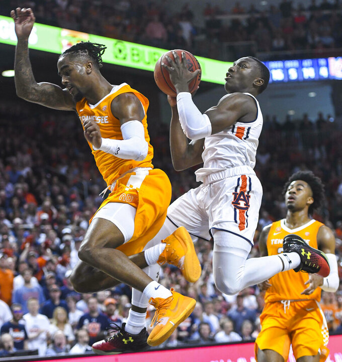 Auburn guard Jared Harper (1) collides with Tennessee guard Jordan Bone (0) on his way to the basket during the second half of an NCAA college basketball game Saturday, March 9, 2019, in Auburn, Ala. (AP Photo/Julie Bennett)