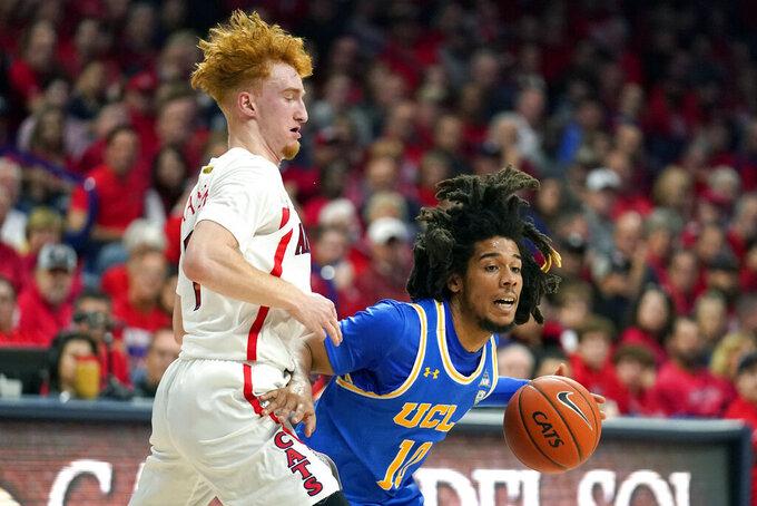 UCLA guard Tyger Campbell (10) drives on Arizona guard Nico Mannion during the first half of an NCAA college basketball game Saturday, Feb. 8, 2020, in Tucson, Ariz. (AP Photo/Rick Scuteri)