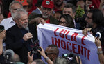 Brazil's former President Luiz Inacio Lula da Silva holds the corner of a banner that reads in Portuguese