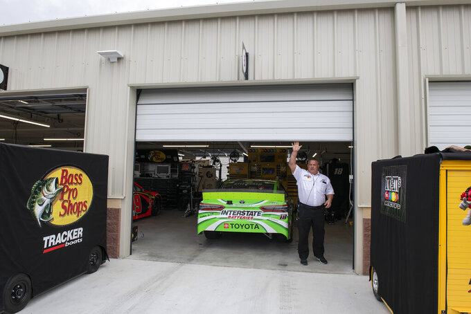 An official opens the door of Kyle Busch's team garage before the Drydene 400 - Monster Energy NASCAR Cup Series playoff auto race, Sunday, Oct. 6, 2019, at Dover International Speedway in Dover, Del. (AP Photo/Jason Minto)